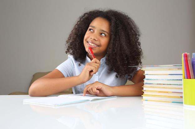 Schulmädchen denkt über hausaufgaben nach, die hausaufgaben machen