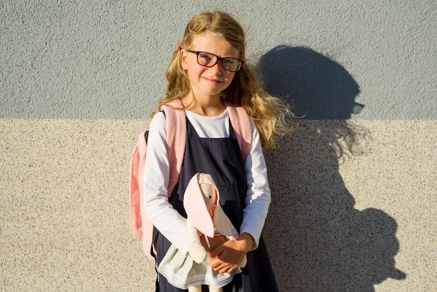 Schulmädchen der grundschule lächelt und hält ein spielzeug.