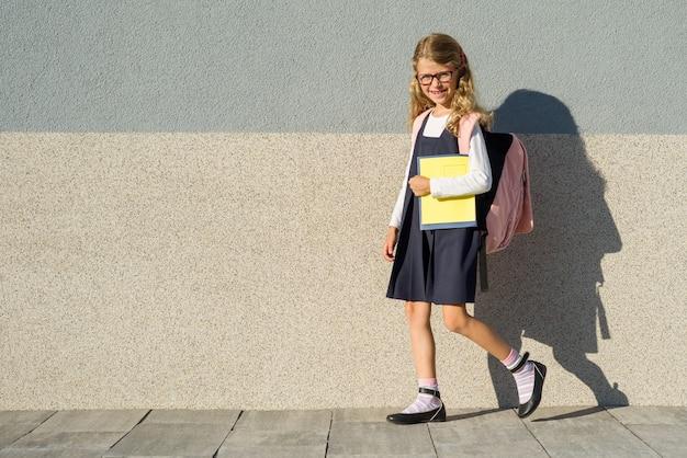 Schulmädchen der grundschule mit notizbüchern in seiner hand