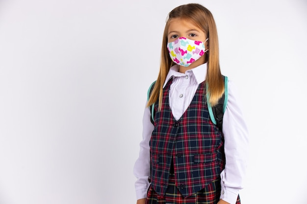 Schulmädchen der grundschulklassen und schuluniform und trägt eine maske, geht zur schule. quarantäne, pandemie. graue wand mit leerem raum.