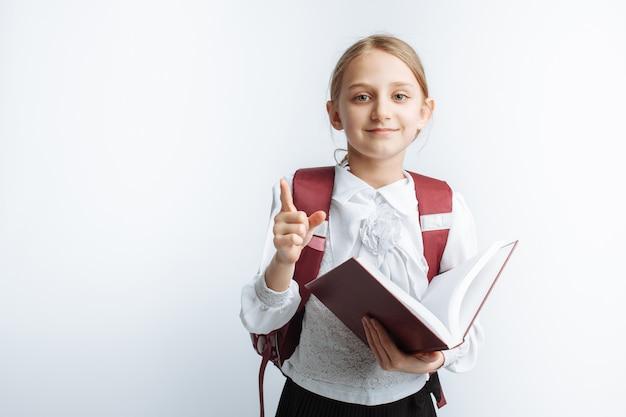 Schulmädchen des kleinen mädchens, das ein buch liest, weiße wand