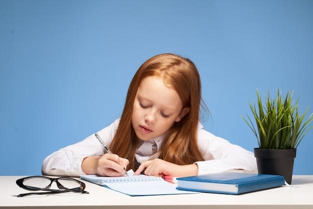 Schulmädchen des kleinen mädchens, das hausaufgaben macht, die an einem tisch sitzen