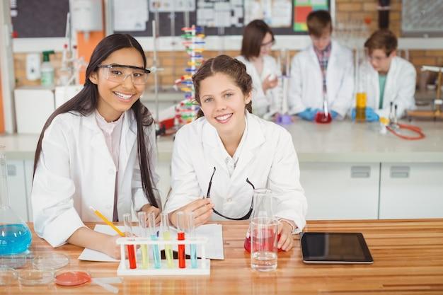 Schulmädchen, die im tagebuch schreiben, während sie im labor in der schule experimentieren