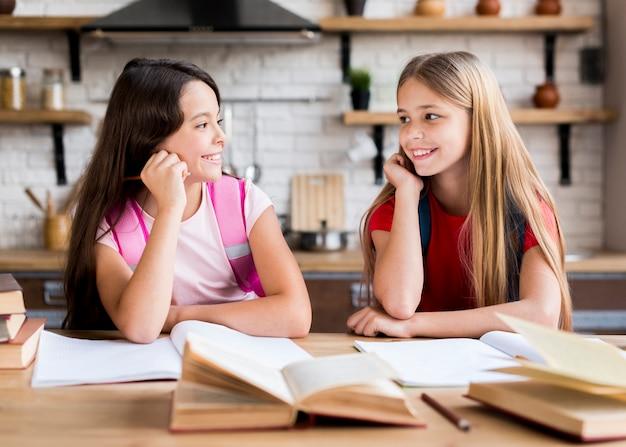 Schulmädchen, die zusammen hausaufgaben machen