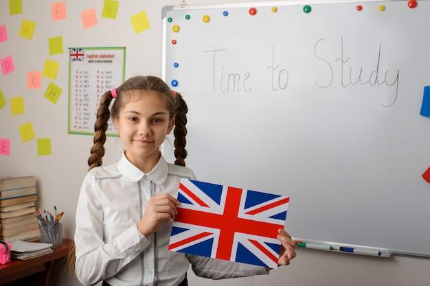 Schulmädchen flagge des vereinigten königreichs, das im klassenzimmer steht