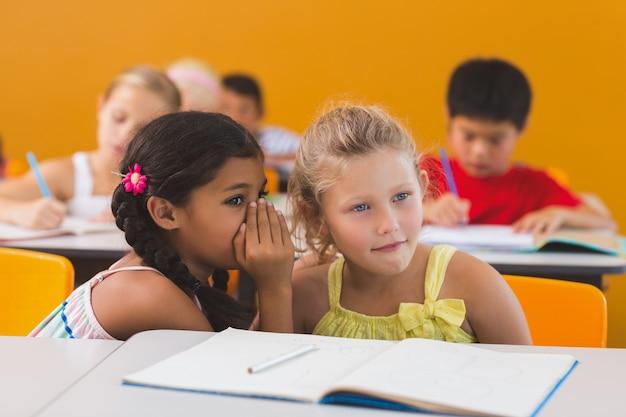 Schulmädchen flüstert ihrer freundin im klassenzimmer ins ohr