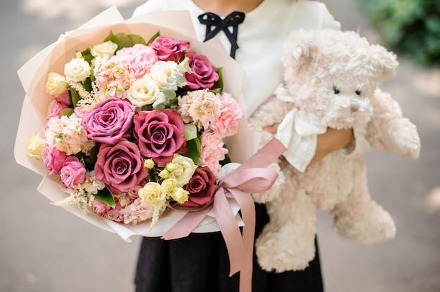 Schulmädchen gekleidet in schuluniform, die einen hellen bunten festlichen blumenstrauß und einen teddybär hält