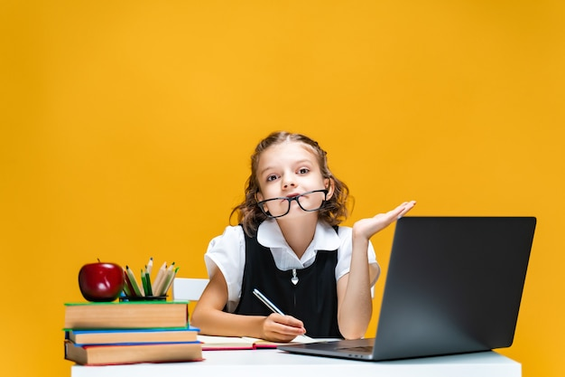 Schulmädchen im spaß am schreibtisch sitzend mit laptop bücher notebook fernunterricht