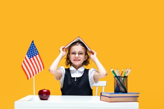 Schulmädchen im spaß, das am schreibtisch sitzt und ein buch auf dem kopf hält englischunterricht usa-flagge