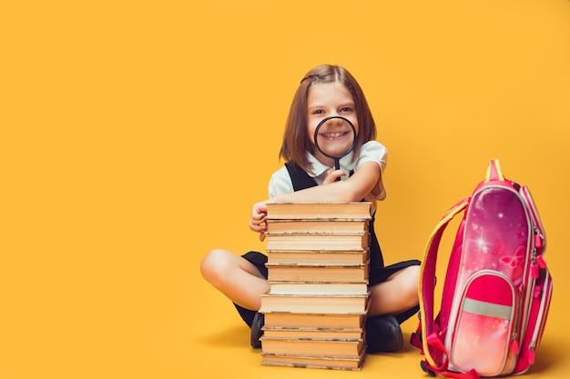 Schulmädchen im spaß, das hinter einem stapel büchern mit lupenkonzept des lernens und der schule sitzt