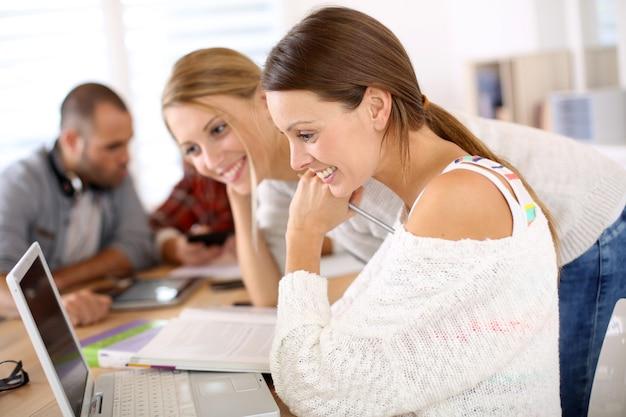 Schulmädchen in der klasse studierend auf laptop-computer