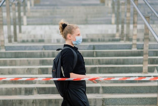 Schulmädchen in der medizinischen schutzmaske bei sonnenuntergang. moderner schüler mit rucksack während der covid-19-quarantäne.