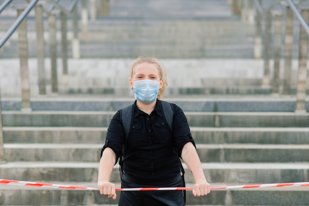 Schulmädchen in der medizinischen schutzmaske bei sonnenuntergang.