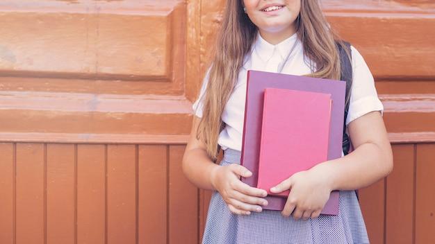 Schulmädchen in der uniform, die bücher und das lächeln hält