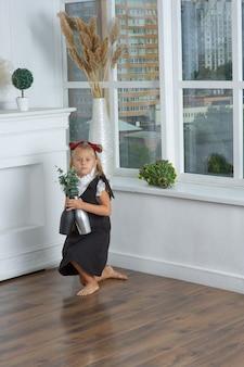 Schulmädchen in einem weißen hemd und einem schwarzen zopf mit topfblumen in ihren händen