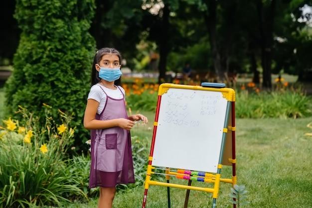 Schulmädchen in einer maske steht und schreibt unterricht an die tafel