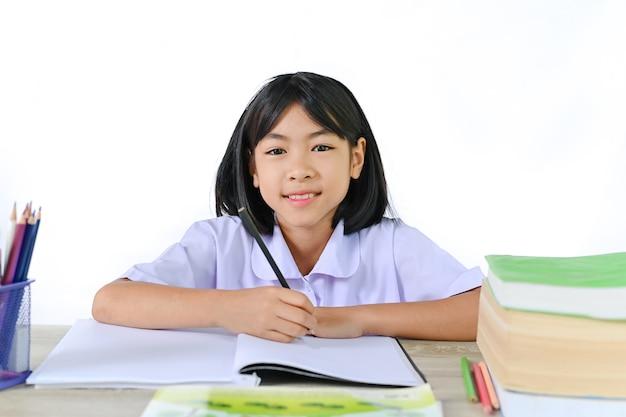 Schulmädchen in einer uniform, die auf schulschreibtisch auf weißem wandkonzept sitzt, das vom lehrer lernt.