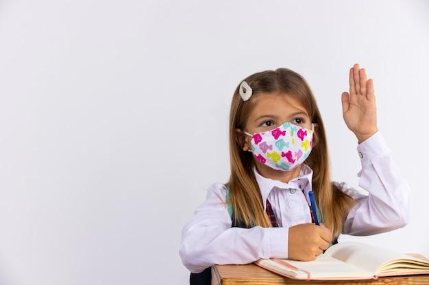 Schulmädchen in medizinischer maske hob im unterricht die hände und trainierte bücher auf dem tisch. schulkonzept