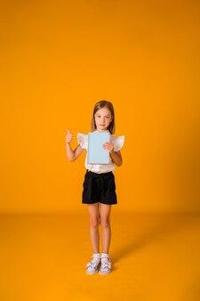 Schulmädchen in uniform steht und hält ein blaues notizbuch auf gelbem hintergrund mit einer kopie des raums. in voller höhe