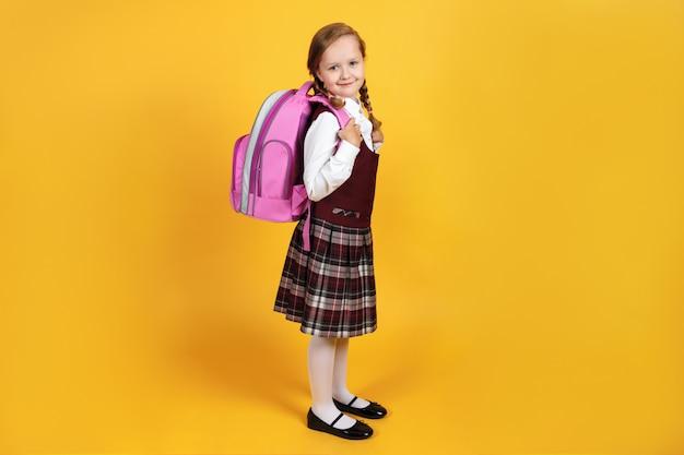 Schulmädchen in voller länge mit einem rucksack hinter ihrem rücken.