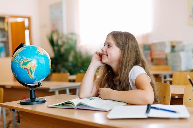 Schulmädchen lächelnd am schreibtisch