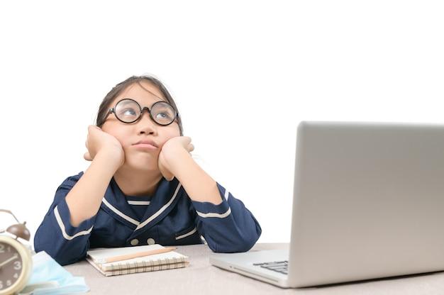 Schulmädchen lernt online-bildungsklassen und fühlt sich gelangweilt und depressiv