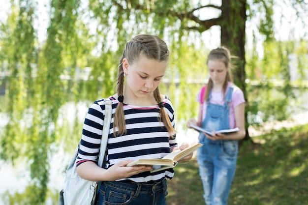 Schulmädchen lesen bücher in der natur