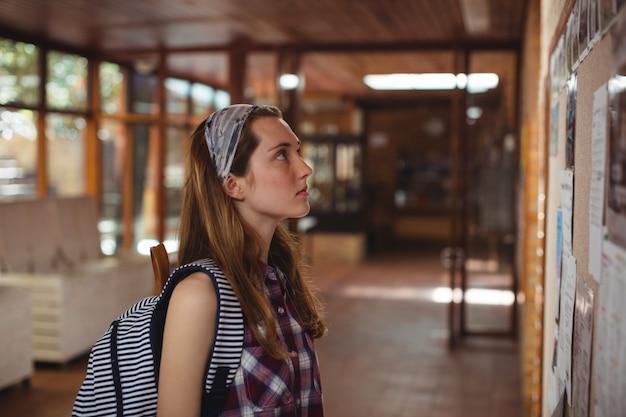 Schulmädchen lesetafel im korridor