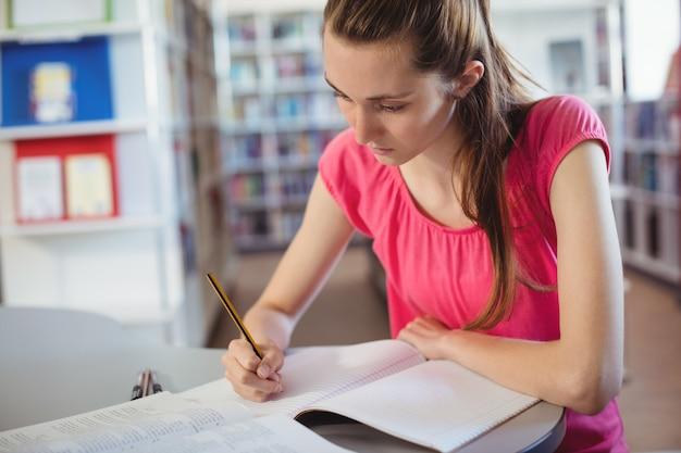 Schulmädchen macht hausaufgaben in der bibliothek in der schule