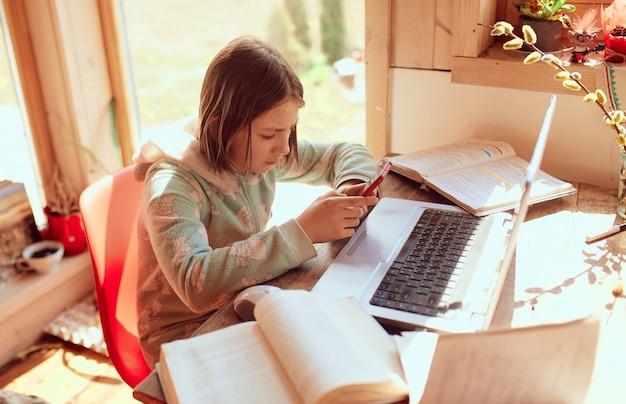 Schulmädchen macht hausaufgaben zu hause und tippt eine nachricht auf ihrem handy