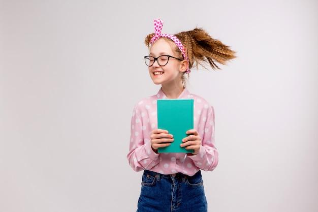 Schulmädchen mit brille mit einem buch lächelnd