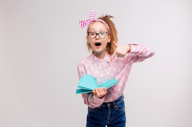 Schulmädchen mit brille mit einem buch