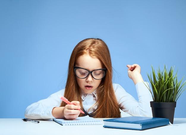 Schulmädchen mit brille sitzt am tisch und macht unterricht lifestyle-training