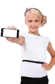 Schulmädchen mit dem handy in der hand, der die kamera betrachtet