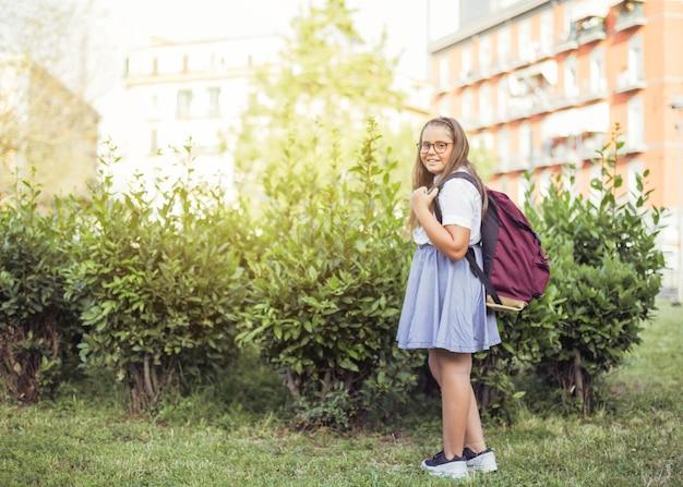 Schulmädchen mit dem rucksack, der vor dem buschlächeln steht