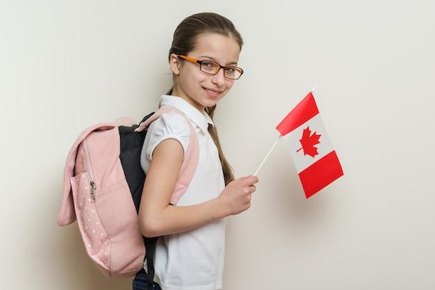 Schulmädchen mit einem rucksack, der die flagge von kanada hält