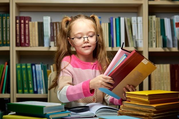 Schulmädchen mit einem stapel bücher in der bibliothek, bereit, neues wissen zu erlangen, sich auf die prüfung vorzubereiten, hausaufgaben zu machen