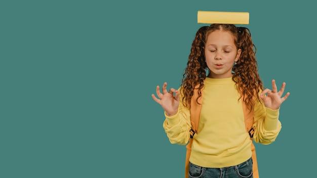 Schulmädchen mit gelbem hemd, das ein buch auf kopfkopierraum hält