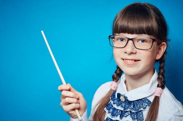 Schulmädchen mit gläsern und einem zeiger auf einem blauen hintergrund