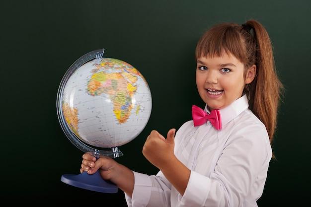 Schulmädchen mit globus zeigt ok zeichen