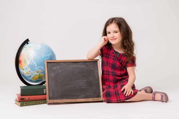 Schulmädchen mit kugel, büchern und leerem reißbrett auf weißem hintergrund