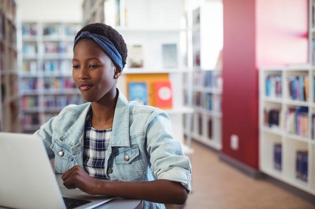 Schulmädchen mit laptop in der bibliothek