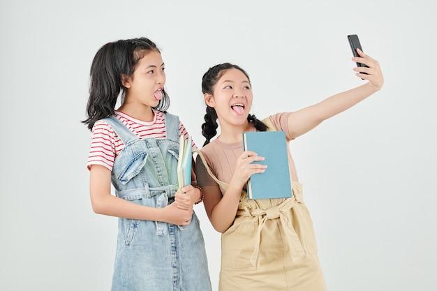 Schulmädchen mit lehrbüchern, die beim selfie nach dem unterricht zungen herausstrecken