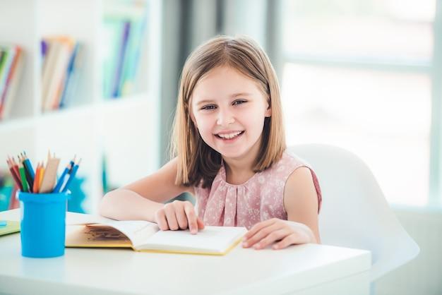 Schulmädchen mit offenem lehrbuch, das am schreibtisch im hellen raum sitzt