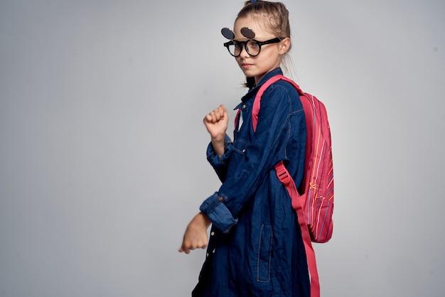 Schulmädchen mit rosa rucksack und sonnenbrille auf grau