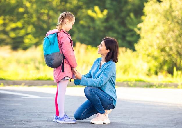 Schulmädchen mit rucksack, das sich vor dem unterricht auf dem parkplatz von der mutter verabschiedet
