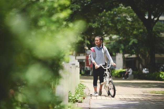 Schulmädchen mit rucksack nach der schule draußen gehend mit ihrem fahrrad