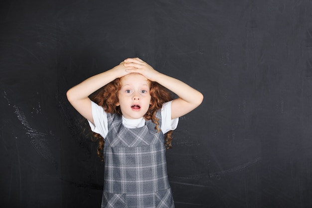 Schulmädchen mit verängstigtem, traurigem, besorgtem betontem ausdruckgesicht.