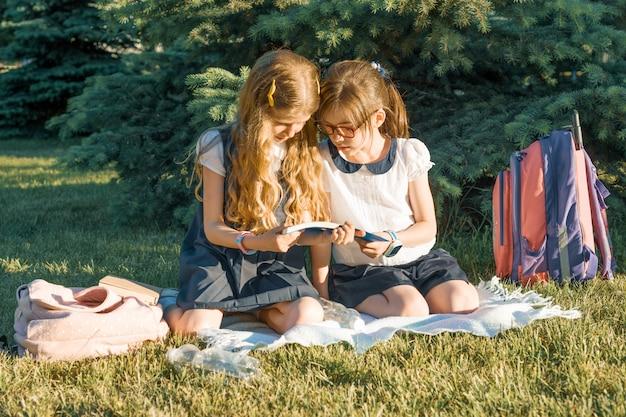Schulmädchen mit zwei kleinen freundinnen, das das sitzen auf einer wiese im park lernt