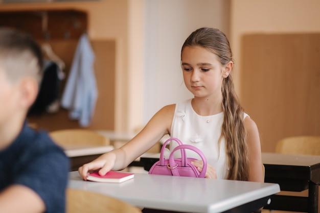 Schulmädchen nimmt ein notizbuch und schreibt hausaufgaben auf